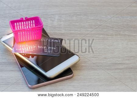 Empty Pink Basket And Mock Up Of Credit Card On Two Smartphones On Wooden Table. Consumers Can Buy P