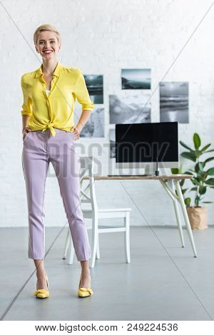 Stylish Smiling Businesswoman With Hands In Pockets Looking At Camera At Office