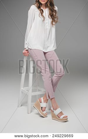 Cropped Image Of Elegant Woman Sitting On Chair On Grey Background