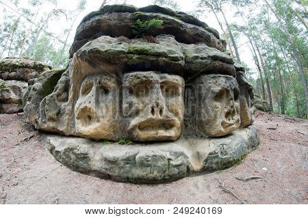 Harpist - Rock Sculptures Of Giant Heads And Other Sculptures Carved Into The Sandstone Cliffs In Th