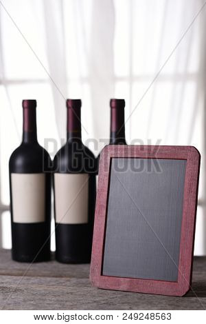 Three bottles of red wine behind a blank chalkboard ready for your copy. Perfect for a Wine Menu or Wine Tasting announcement.