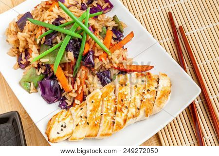 Rectangular Plate Of Delicious Fried Rice With Vegetables And Chicken Breast Close-up