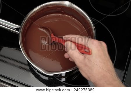 100% Cocoa And Water Being Stirred With A Red Spoon In A Pan By A Hand Of An Adult Male Closeup. Han