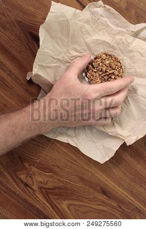 Granola Mix Treat In A Small Clear Plastic Container Being Held By An Adult Male Hand. Sweet Granola