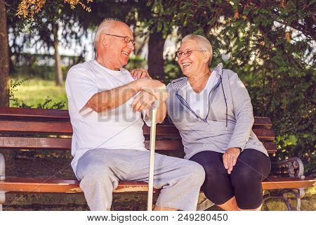 Smiling Senior Couple Sitting Together On A Park Bench