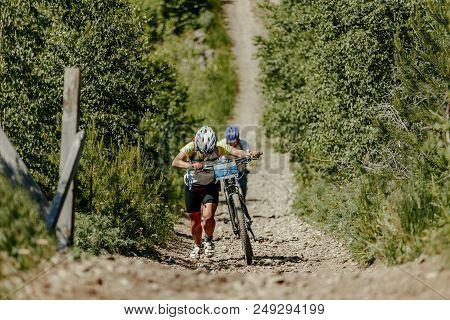 Woman And Man On Bike Uphill Trail Race Mountain Bike