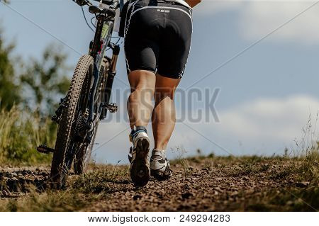 Back Woman Cyclist And Mountain Bike Climbing Uphill On Mountain Trail