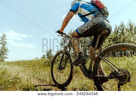 Dirty Male Cyclist With Backpack Riding Trail On Mountainbike