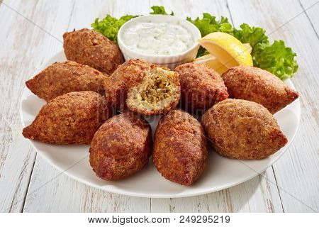 Delicious Kibbeh Stuffed With Fried Beef Ragout And Pine Nuts Served On A White Plate With Lettuce A