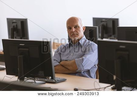 Man Looking At Camera With Arms Folded While Sitting At Desktop