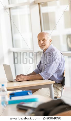 Man Seated Working On Laptop Computer.