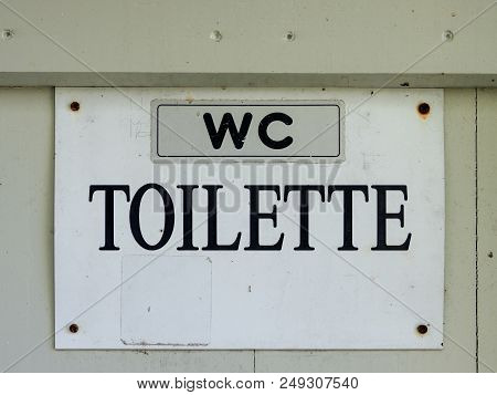 White Sign With Black Lettering Of An Old Toilet