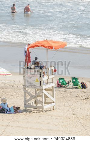 Virginia Beach, Va-august 31, 2017:  Lifeguard Watches Swimmers From Lifeguard Booth A On The Beach