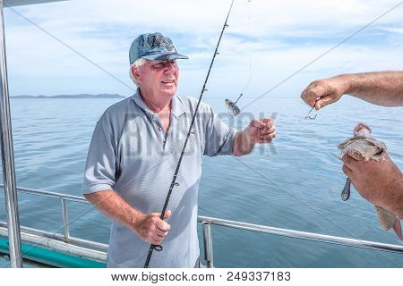 Fisherman Helping Caucasian Tourist On Fishing Charter Boat Taking Hook Out Of Snapper Fish - At Dou
