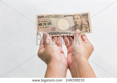 Businesswoman Giving Money And Holding 10,000 Japanese Yen Money In Hand Isolated On White Backgroun