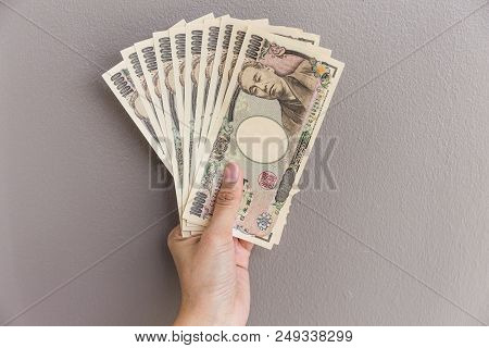 Businesswoman Giving Money And Holding 10,000 Japanese Yen Money In Hand On Gray Wall Background, Ja