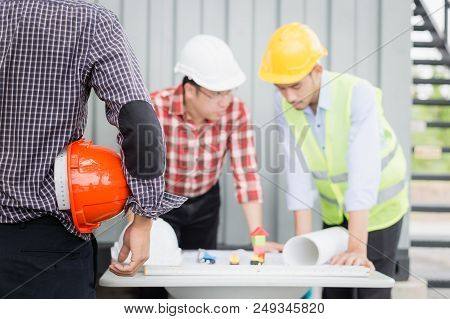 Engineer And Construction Team Wearing Safety Helmet And Looking Blueprint On The Table. They Are Wo