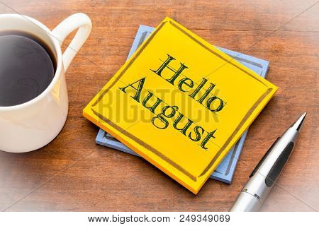Hello August - text on a sticky note against rustic wood with a cup of coffee