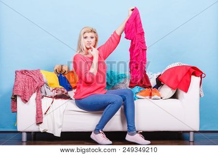 Style Dilemmas Concept. Woman Does Not Know What To Wear Sitting On Messy Couch With Piles Of Clothe