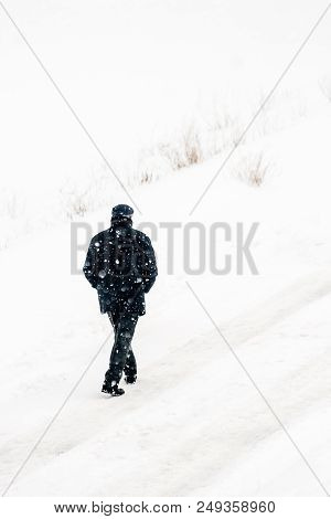 Man Walking The Road In Extreme Snow And Cold