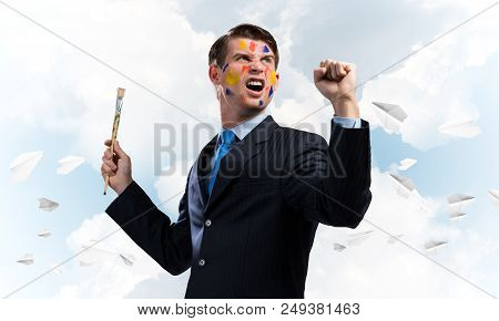 Happy businessman in suit smiling and gesturing while standing with paintbrush in his hand against cloudy skyscape with flying paper planes view on background. poster
