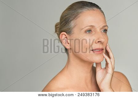 Portrait of mature woman with bare shoulder isolated on gray background. Beautiful middle aged female touching her face skin with copy space. Closeup of senior woman looking at wrinkles, aging process