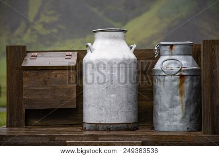 Old Milk Cans Sitting On A Wooden Structure
