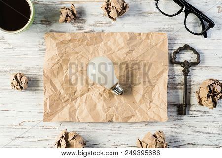 Top view of modern creative workplace with lightbulb on creased piece of sheet, crumpled paper balls, key and cup of coffee placed on wooden table. Concept of finding of outstanding idea. poster