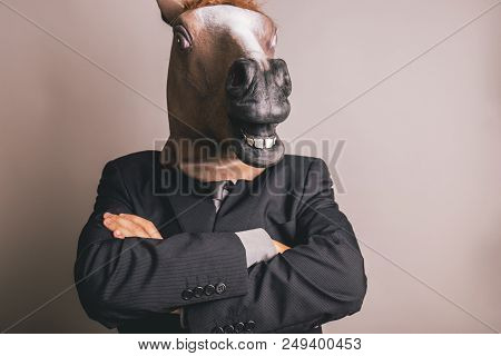 Unidentified Person With A Dark Grey Suit And Tie Wearing A Horse Mask Crossing Arms