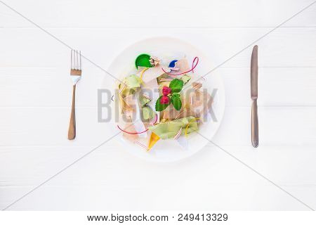 Top view served with knife and fork plate with unreal salad from recycle waste, synthetic ingredients. Concept of artificial, food. GMO, E numbers . Use of chemicals in the food industry. Copy space poster