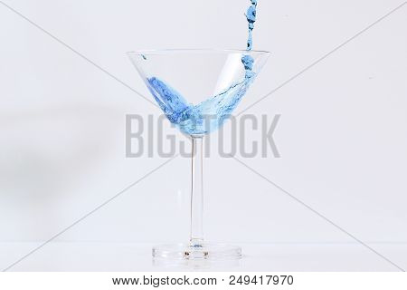 Cocktail With Blue Liquid In Glass. Glass With Blue Water Pouring With Liquid With Splashes And Drop