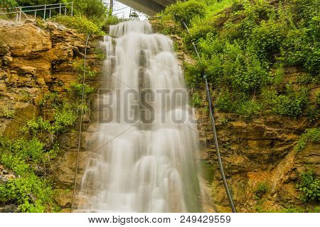 Beautiful Natural Waterfall Cascading Down Mountain Hillside Covered In Lush Green Foliage,