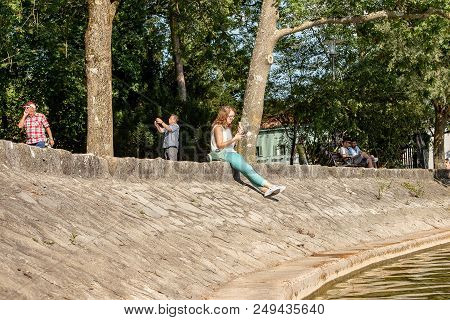 Hersching,germany-july 14,2018:a Woman Eats An Ice Cream While Texting On Her Mobile Phone