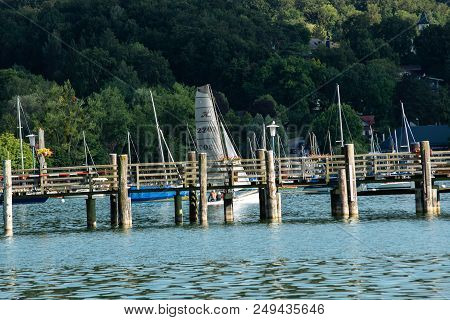 Hersching,germany-july 14,2018:a Sailboat Sails Past Other Boats On A Warm Afternoon At Lake Ammerse