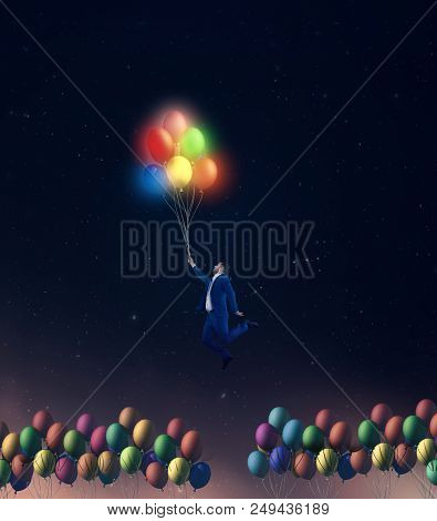 Man Flying With Colorful  Glowing Balloons. Out Of The Box Concept.
