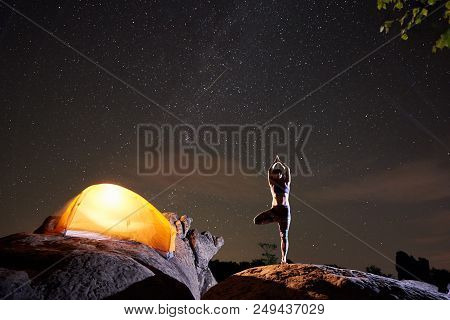Brightly Lit Tourist Tent And Young Slim Woman Standing On One Leg With Raised Arms Doing Yoga At Ni