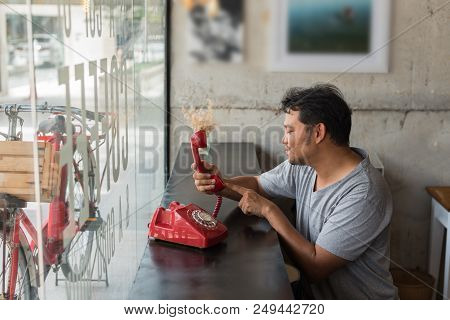 Asian man 40s in gray t-shirt happiness with shy and inlove between waiting something or waiting phone call from lover in a coffee shop cafe with a red telephone vintage style poster