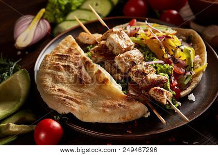 Exotic Still Slife With Pita On An Old-fashioned Plate, Fresh Vegetables And Yummy Kebab Over Vintag