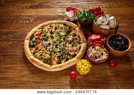 Pizza Still Life. Freshly Baked Italian Pizza And Its Components Arranged On Wooden Background, Top