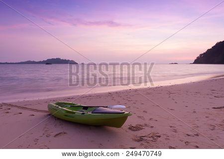 Canoe On The Beach At Twilight Time.