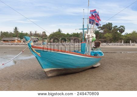 Blue Wooden Fishing Boat On The  Low Tide Beach.