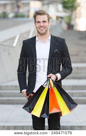 Exclusive Shopping. Man Shopper Carries Shopping Bags Urban Background. Successful Businessman Choos