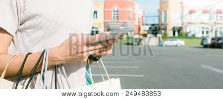 Young Woman Hold A Shopping Bags In Her Hand And Chatting On Her Phone After Shopping. Young Woman S
