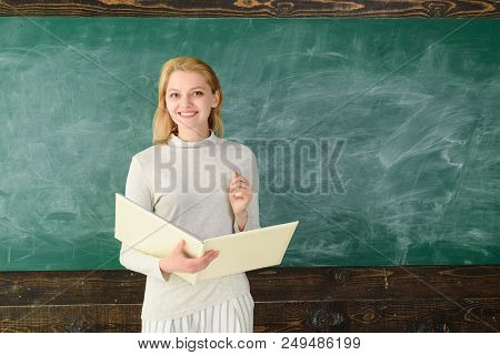 Portrait Of Young Teacher In Classroom. Young Satisfied Professor. Prof With Folder. Portrait Of Fem