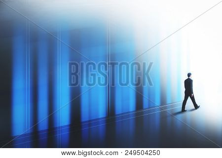 Success Concept With Businessman Walking Towards His Ambition Along The Wall To The Light Side
