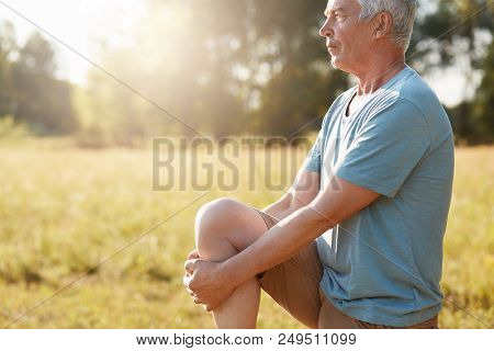 Cropped Shot Of Serious Mature Male Stretches Legs On Green Field, Looks Into Distance, Does Physica