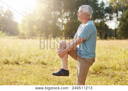 Sideways Shot Of Healthy Elderly Male Stretches Legs, Has Serious Expression, Wears Sport Clothes An