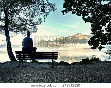 Man Sit On Wooden Bench At Coast Of Picturesque Lake Bellow Blue Mountain Summits. Calmness, Silence