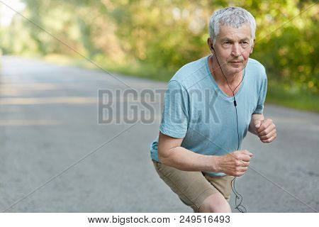 Retired Confident Male Stands On Start, Ready To Take Part In Sport Comeptitions, Listens Music With