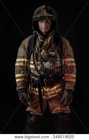 Serious Dirty Man In Uniform Of Firefighter And Helmet Standing On Black Background Looking Seriousl